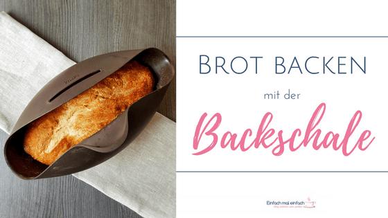 """Brot in der Backschale auf hellem Baumwolltuch und grauem Untergrund. Text:""""Brot backen mit der Backschale."""""""