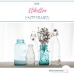 """Saubere Gläser und Flaschen aus hellblauem und weißem Glas mit Trockenblumen vor hellem Hintergrund. Text:""""DIY Etikettenentferner"""""""
