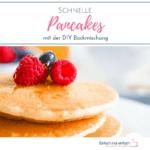 Stapel amerikanscher Pancakes auf einem weißen Teller mit Himbeeren und Blaubeeren dekoriert.