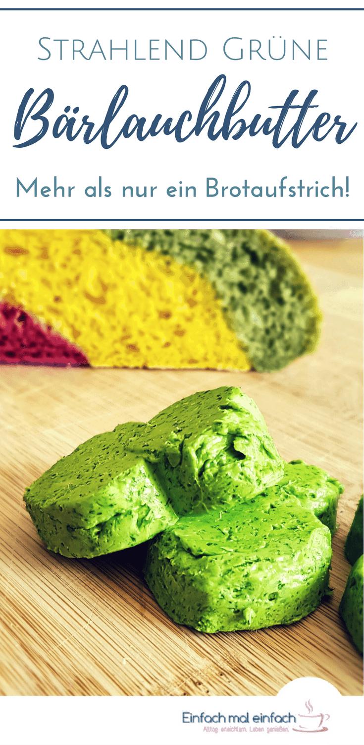 Grüne Bärlauchbutterformen auf Holzbrett mit buntem Brot im Hintergrund.