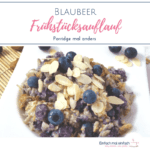 Blaubeer-Frühstücksauflauf auf weißem Teller mit frischen Blaubeeren und Mandelblättchen dekoriert und Schalen mit Mandeln und Hafergrütze im Hintergrund.