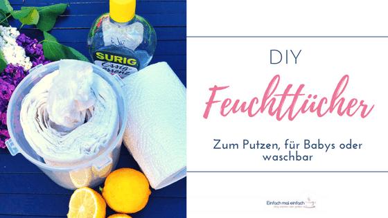 Box mit DIY Feuchttüchern, Küchenrolle, Essigflasche und Zitronen auf dunklem Untergrund mit Flieder im Hintergrund. Text