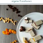 Fruchtriegel mit Oblaten in drei Varianten - tropisch-gelb, beerig-rot und schokoladig, umgeben von Nüssen, Cranberries, Schokolade, Mandeln und Kokosraspeln auf grauem Untergrund.