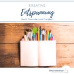 """Leeres, aufgeschlagenes Notizbuch auf bunten Stiften und Pinseln vor Holzuntergrund. Text:""""Kreative Entspannung durch Ausmalen und Tanglen"""""""