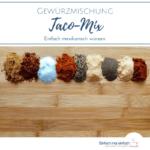 """Taco-Gewürze in einer Reihe auf hölzernem Schneidbrett. Text:""""Gewürzmischung Taco-Mix. Einfach mexikanisch würzen"""""""