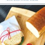 Weißes Kastenbrot auf Holzbret mit Sandwich in Butterbrottüte und rotem Garn zugebunden. Tomaten, Salat und dunkle Soße auf dem belegten Brot.