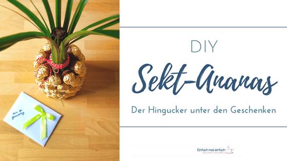 """Mit Rocher beklebte Sektflasche zur Ananas gestaltet auf Holztisch von oben. Text:""""DIY Sekt-Ananas - Der Hingucker unter den Geschenken."""""""