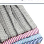 """Bunt gestreifte Wäsche gestapelt vor hellem Hintergrund. Text:""""Glücklich ohne Bügeleisen. Glatte Wäsche geht auch anders."""""""