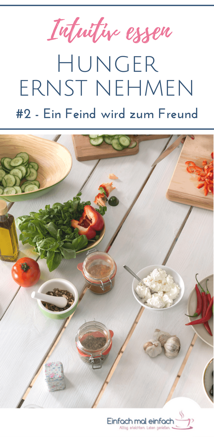 """Lebensmittel dekorativ auf einem weißen Holztisch. Text:""""Intuitiv essen - Hunger ernst nehmen - #2 - Ein Feind wird zum Freund"""""""