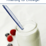 """Joghurtglas mit Löffel vor hellem Hintergrund mit Beeren. Text:""""Joghurt selber machen. Anleitung für Einsteiger."""""""