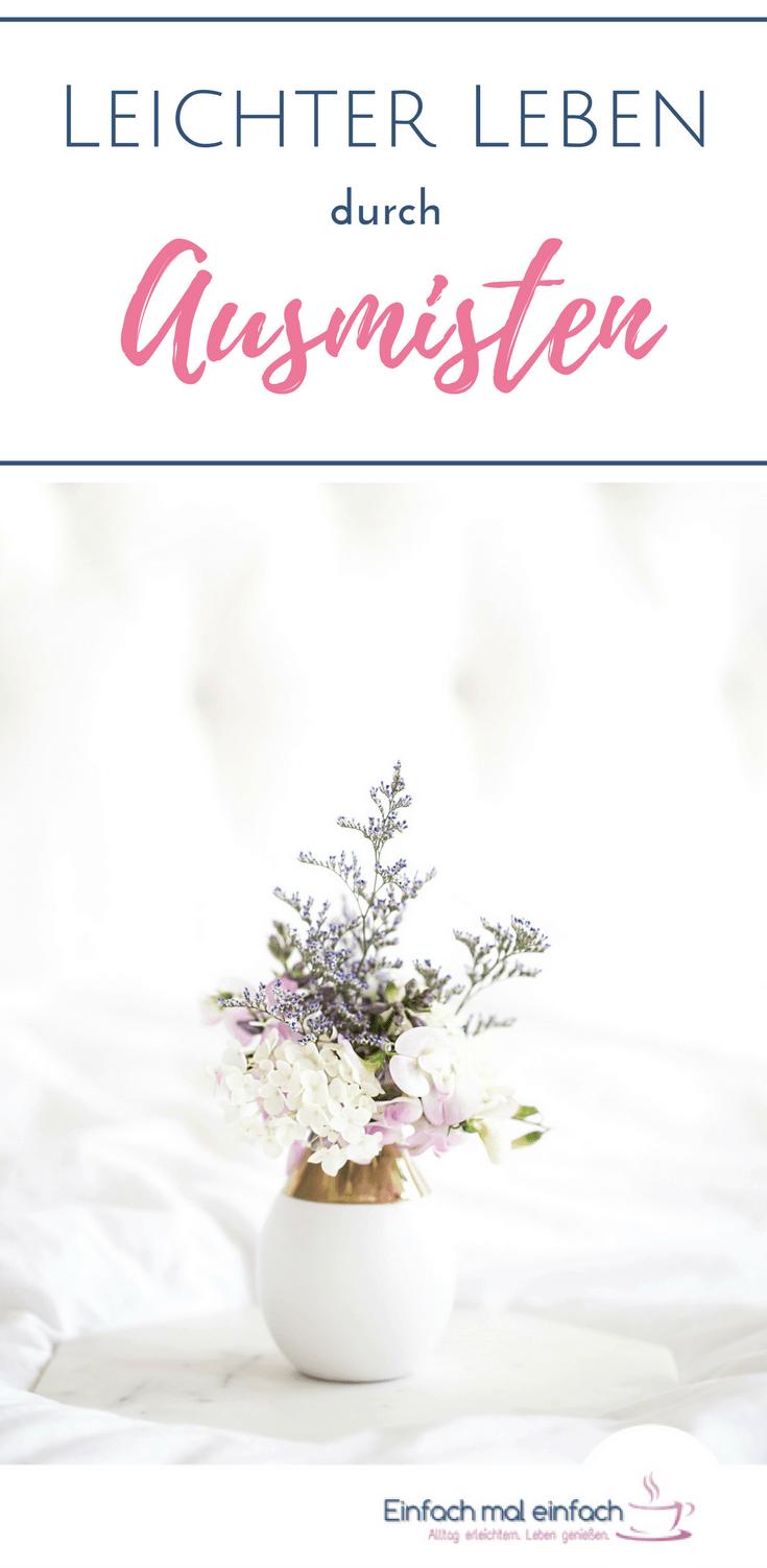 """Weiße Vase mit lila und weißen Blumen auf Marmortablett vor hellem Hintergrund. Text:""""Leichter Leben durch Ausmisten"""""""