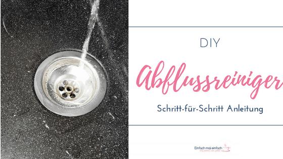 """Abfluss in dunkler Granitspüle, Wasser einlaufend. Text:""""DIY Abflussreiniger Schritt-für-Schritt Anleitung."""""""