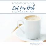 """Weiße Kaffeetasse auf Untertasse und lachsfarbenem Notizbuch. Text:""""Adventskalender Zeit für Dich - Entspannt durch die Adventszeit"""""""