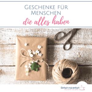"""Geschenk in Naturpapier mit Garn und Blüten dekoriert auf Holzuntergrund mit Schere und Garnrolle. Text:""""Geschenke für Menschen die alles haben."""""""