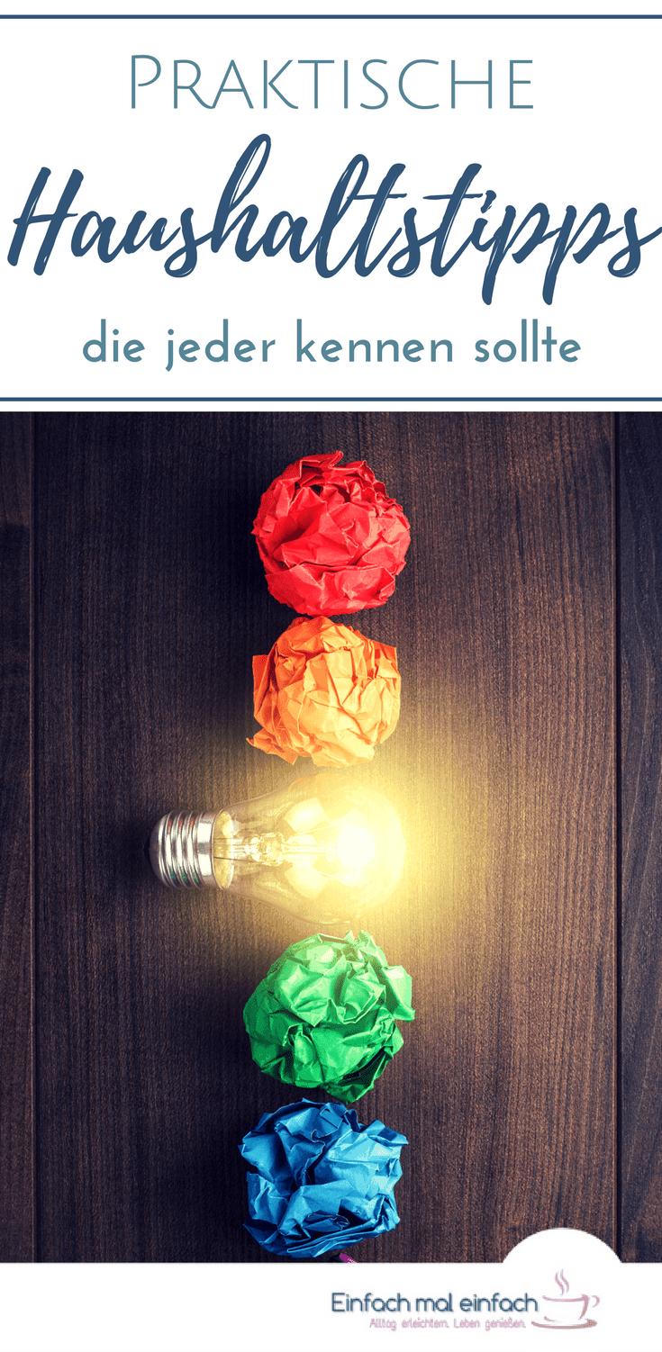 """Bunte Bälle aus zerknülltem Papier in Regenbogenfarben mit leuchtender Glühbirne in einer Reihe auf dunklem Holzuntergrund. Text:""""Praktische Haushaltstipps die jeder kennen sollte."""""""