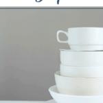 """Weißes Geschirr hoch aufgestapelt auf heller Oberfläche mit grauem Hintergrund. Text:""""Haushaltstipps zum Platzsparen."""""""