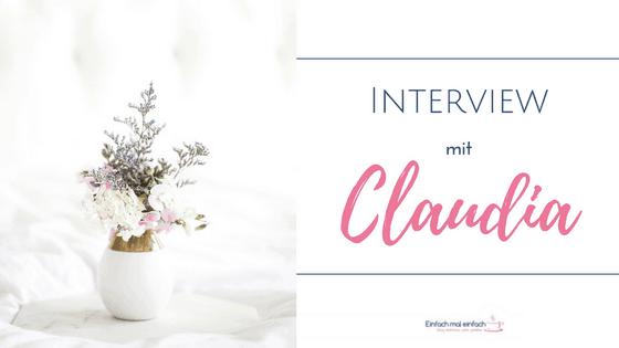 """Weiße Vase mit lila und weißen Blumen auf Marmortablett vor hellem Hintergrund. Text:""""Interview mit Claudia"""""""