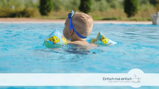 Kleinkind im Pool mit Schwimmflügeln und Sonnenbrille